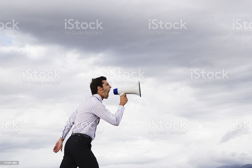 Man with megaphone shouting outdoors royalty-free stock photo