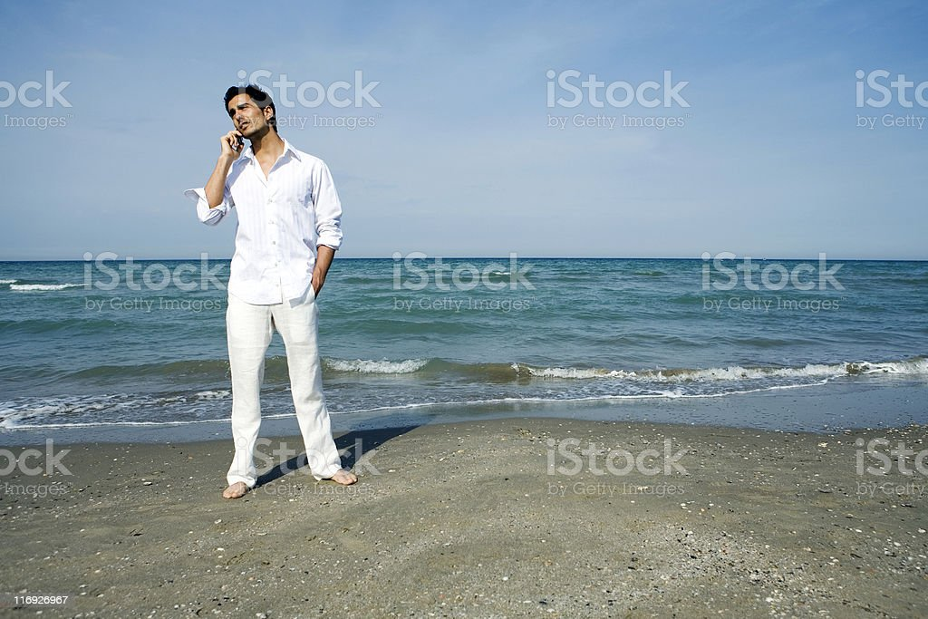 Man with mobile phone at the beach royalty-free stock photo