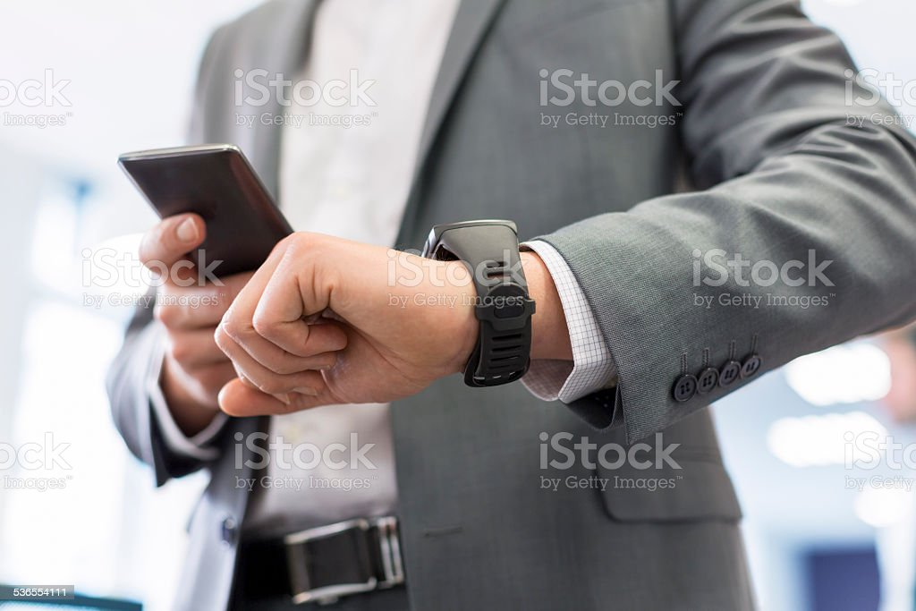Man with Mobile phone connected to a smart watch stock photo
