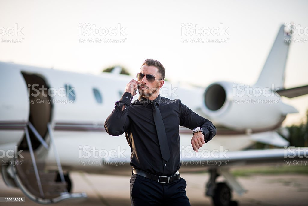 Man with mobile phone in front of jet airplane stock photo