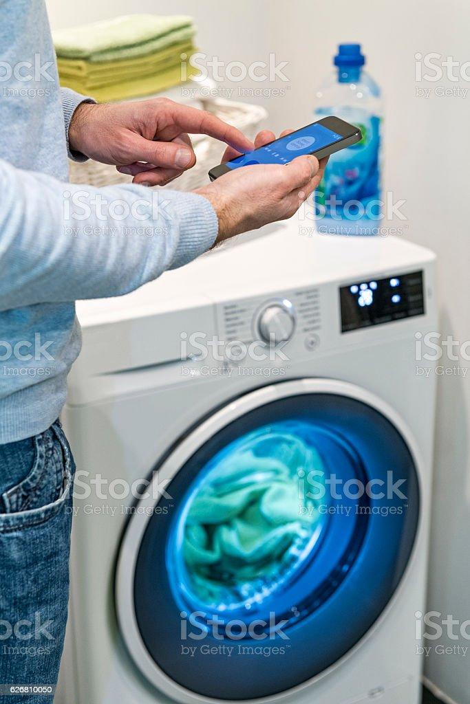 Man with mobile phone smart control home washing machine, bathroom stock photo