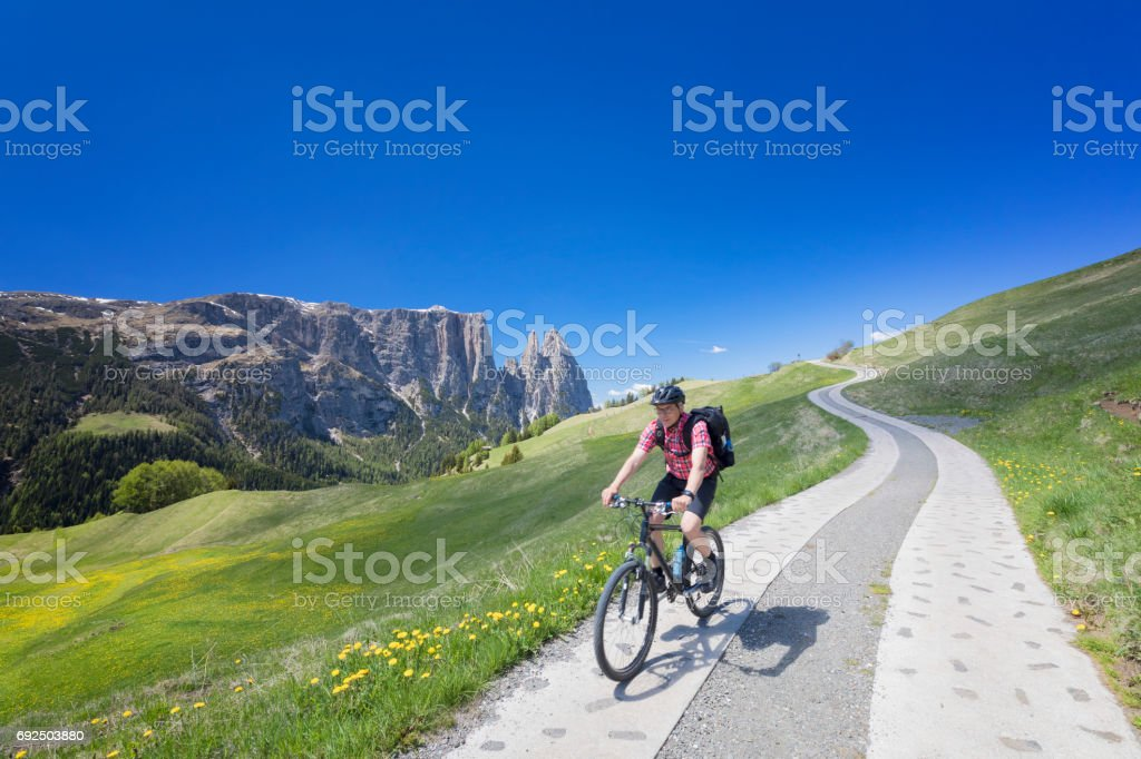Man with Mountain bike at Alpe di Siusi - Mount Schlern in background stock photo