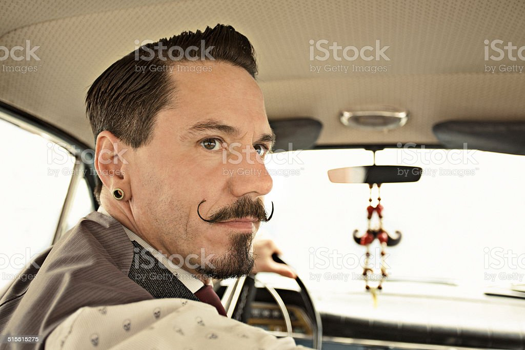 Man with moustaches driving  car stock photo