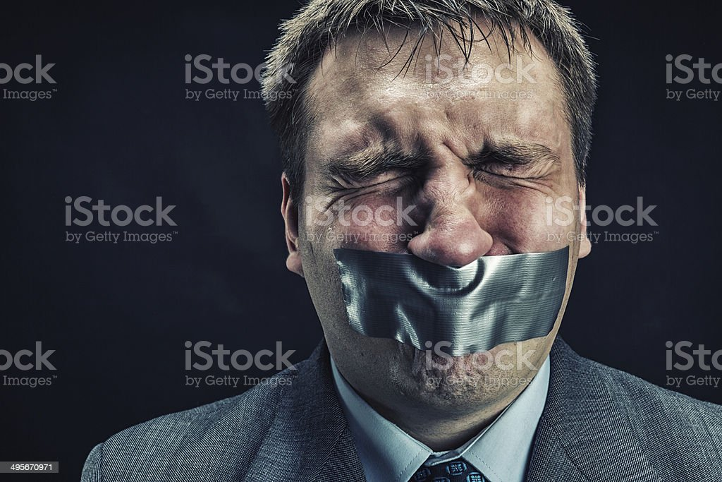 Man with mouth covered by masking tape stock photo