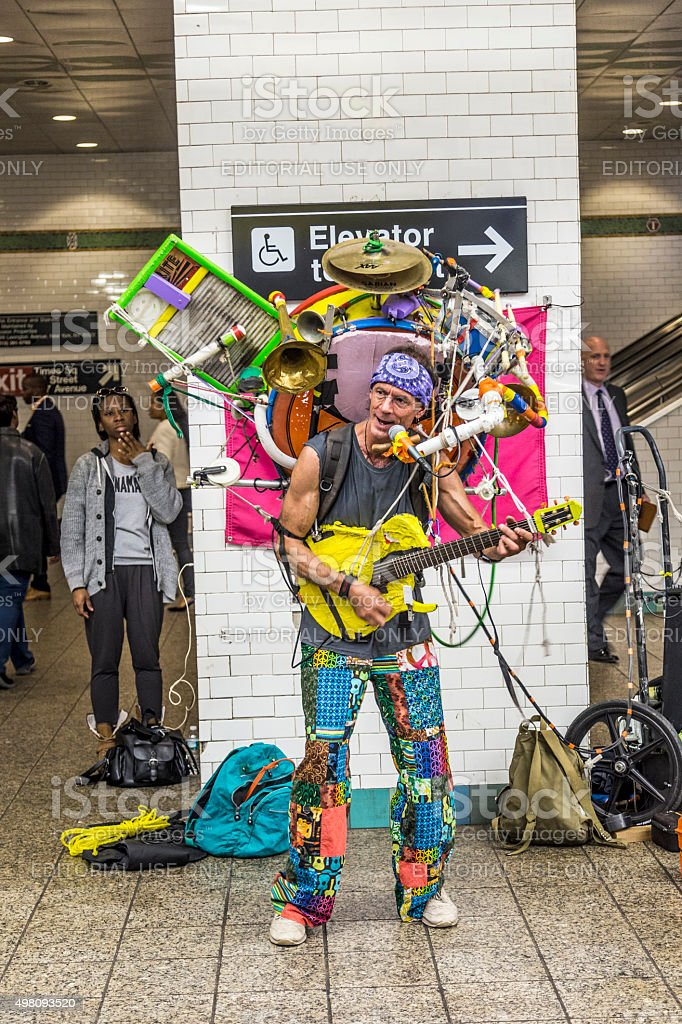 man with multiple music instruments performing at Metro station stock photo