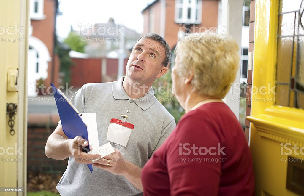 Man with name tag and clipboard talking to woman stock photo