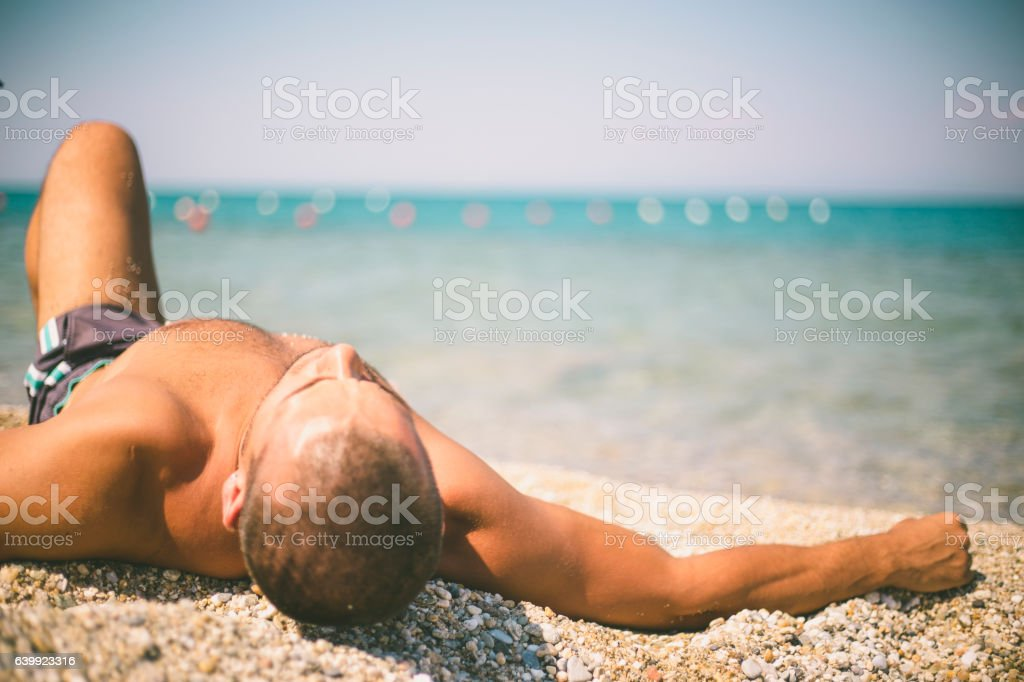 Man with no shirt lay down on the beach stock photo