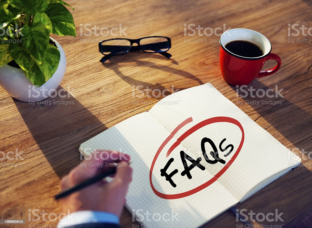 Man with Note Pad and FAQs Concepts stock photo