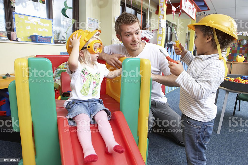 Man with nursery children playing together royalty-free stock photo