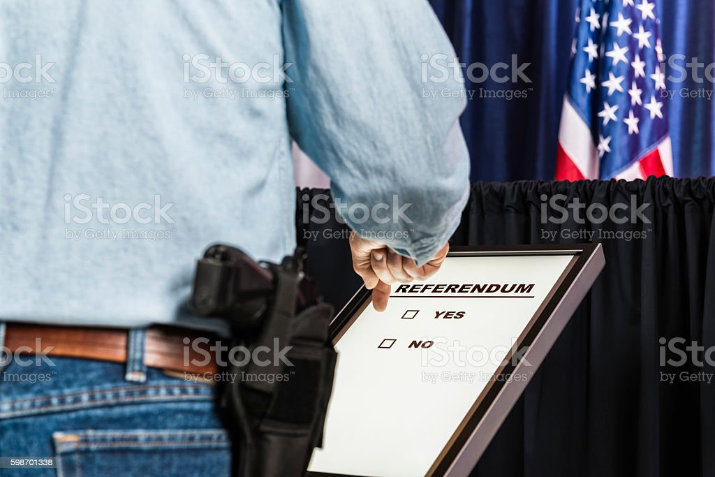 Man with open-carry handgun in holster looking over Referendum ballot stock photo