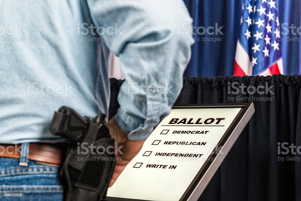 Man with open-carry handgun in holster looking over voting ballot stock photo