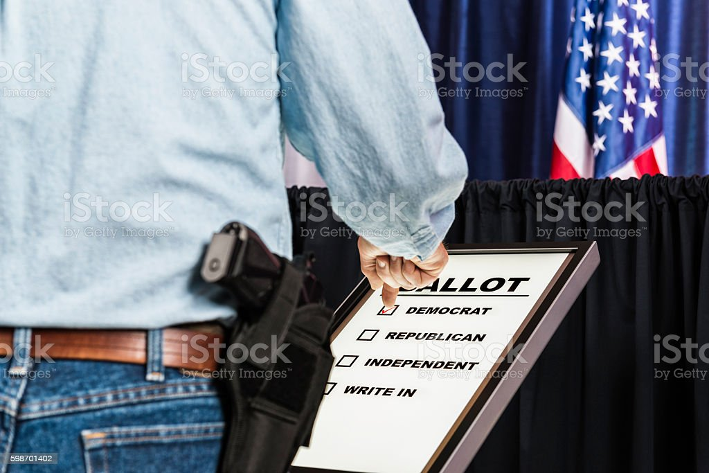 Man with open-carry handgun in holster voting for Democrat candidate stock photo