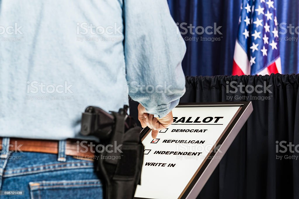 Man with open-carry handgun in holster voting for Republican candidate stock photo