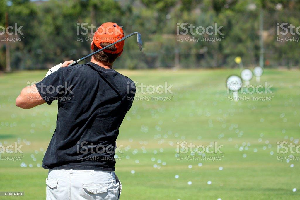 Hombre en el campo de práctica de golf foto de stock libre de derechos