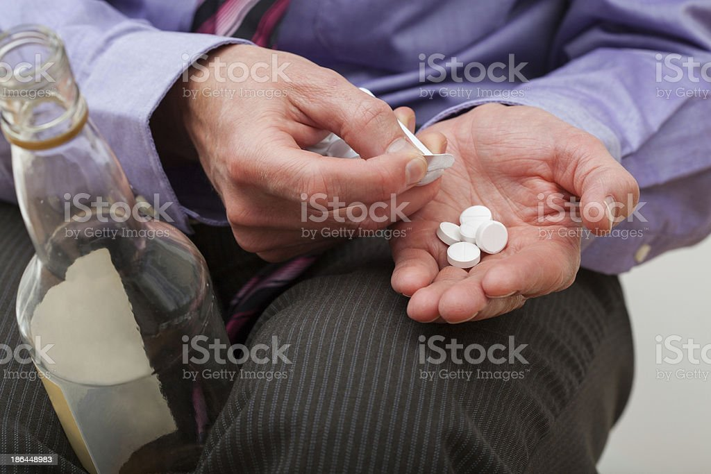 Man with painkillers and alcohol royalty-free stock photo