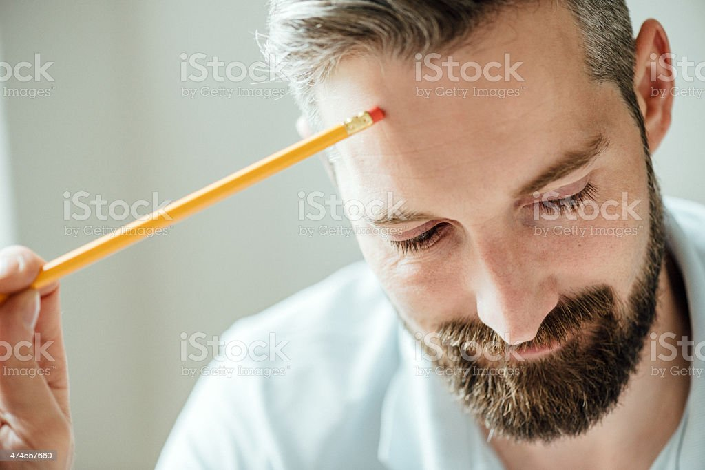 Man with pen studying at desk stock photo
