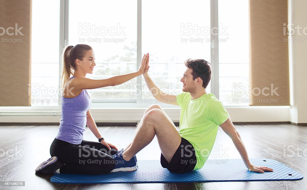 man with personal trainer doing sit ups in gym stock photo