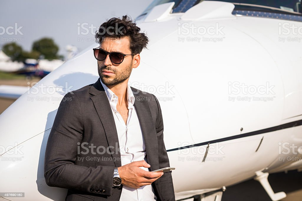 Man with phone next to private jet aeroplane stock photo