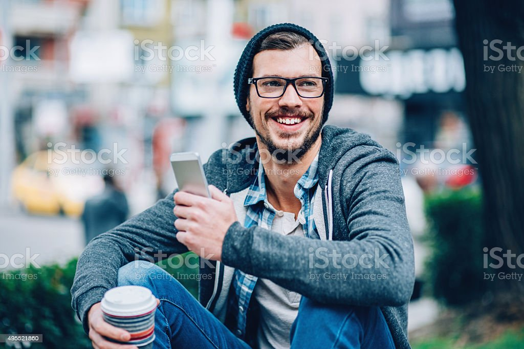 Man with phone outdoors stock photo