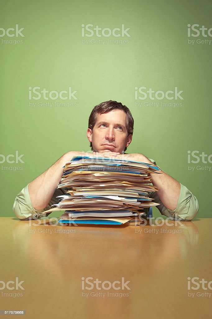 Man with piles of work stock photo