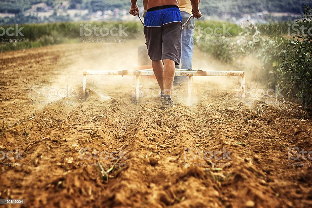 man with plough machine working the soil stock photo