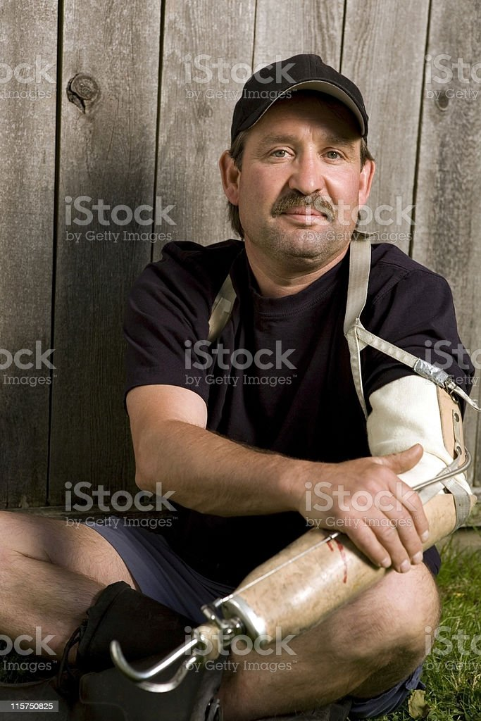 Man with prosthetic arm sitting on lawn. royalty-free stock photo