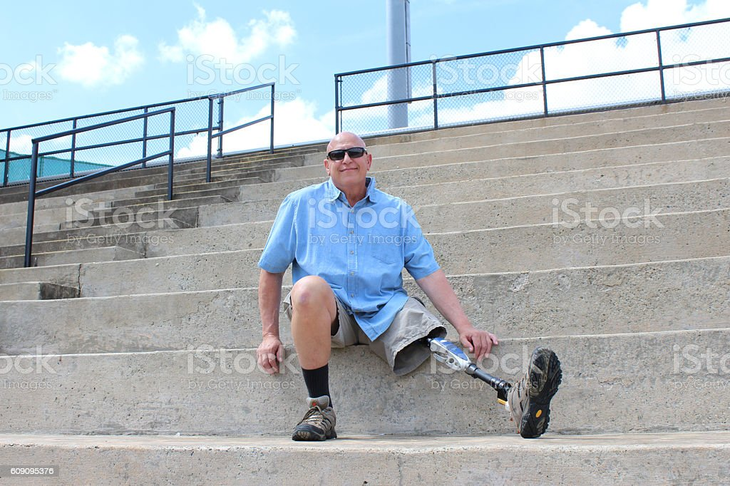 Man with prosthetic leg seated on concrete bleachers stock photo