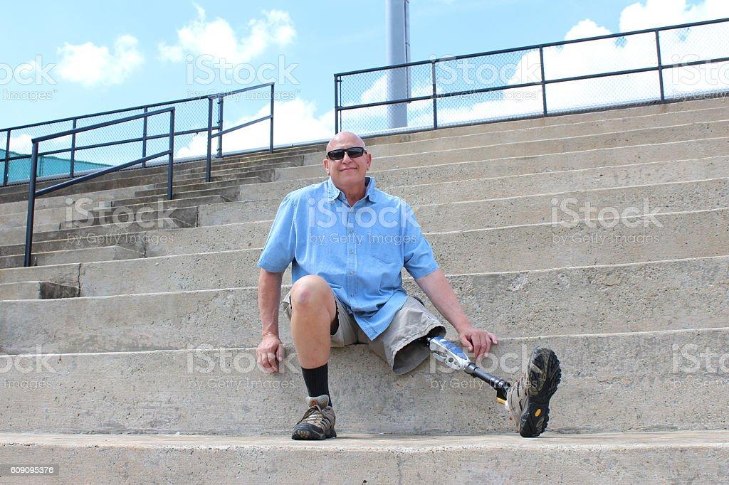 Man with prosthetic leg seated on concrete bleachers stock photo