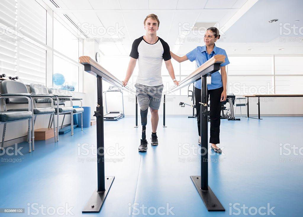 Man with prosthetic leg using parallel bars with physyiotherapist stock photo