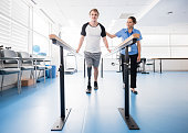 Man with prosthetic leg using parallel bars with physyiotherapist