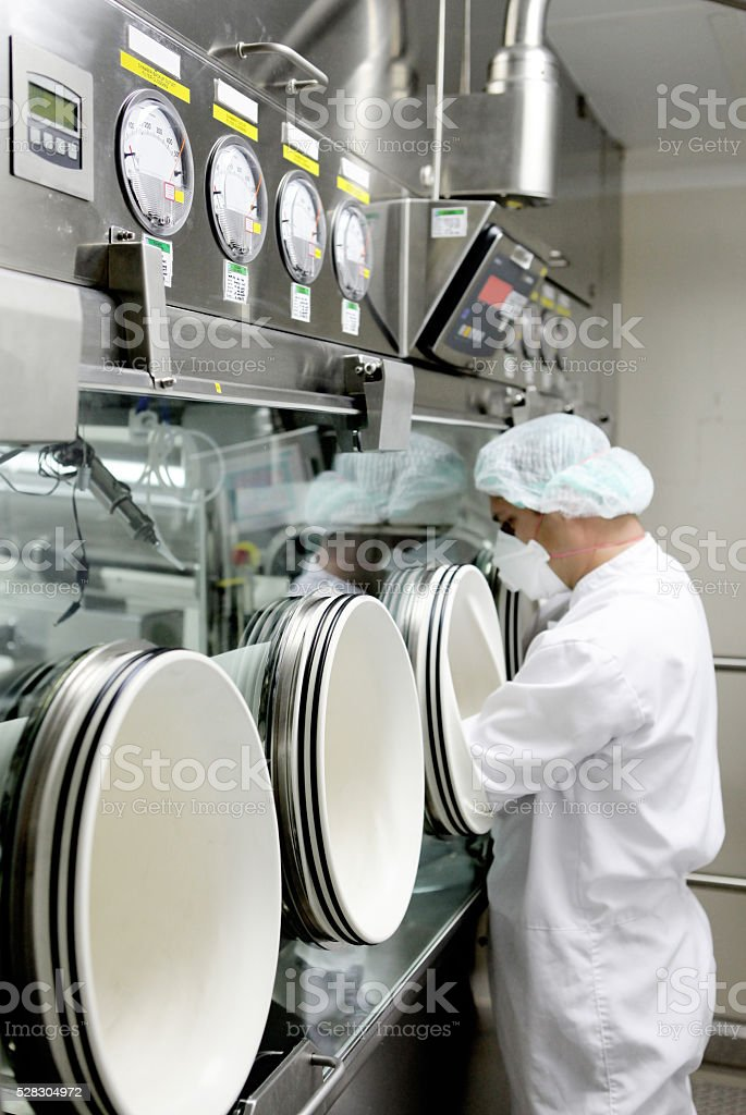 Man with protective clothes in front of anaerobic chamber stock photo