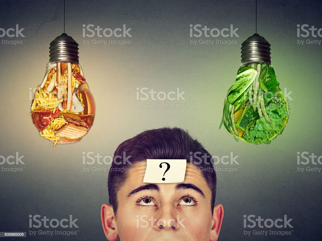 man with question looking at junk food vegetables light bulbs stock photo