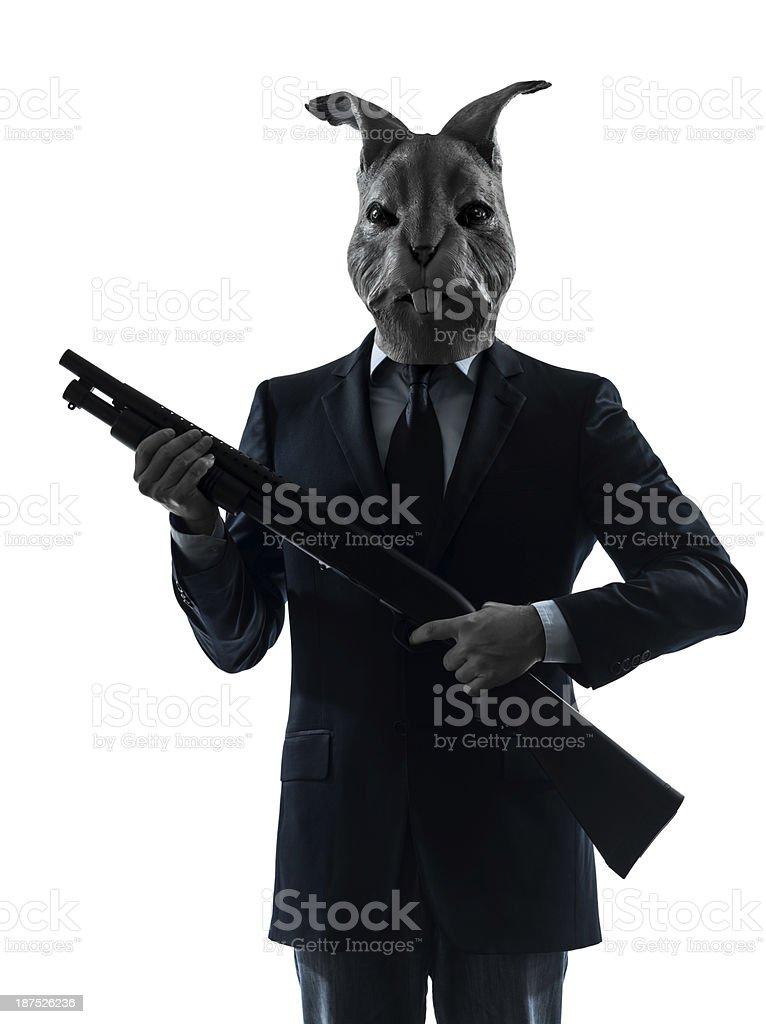 man with rabbit mask hunting shotgun silhouette portrait stock photo