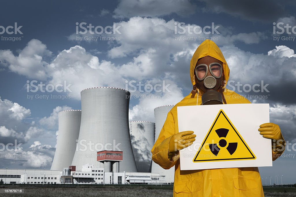 Man With Radioactive Sign in Front of Nuclear Reactor stock photo
