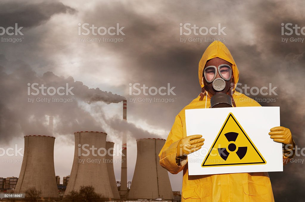 Man with radioactivity sign and nuclear plant stock photo
