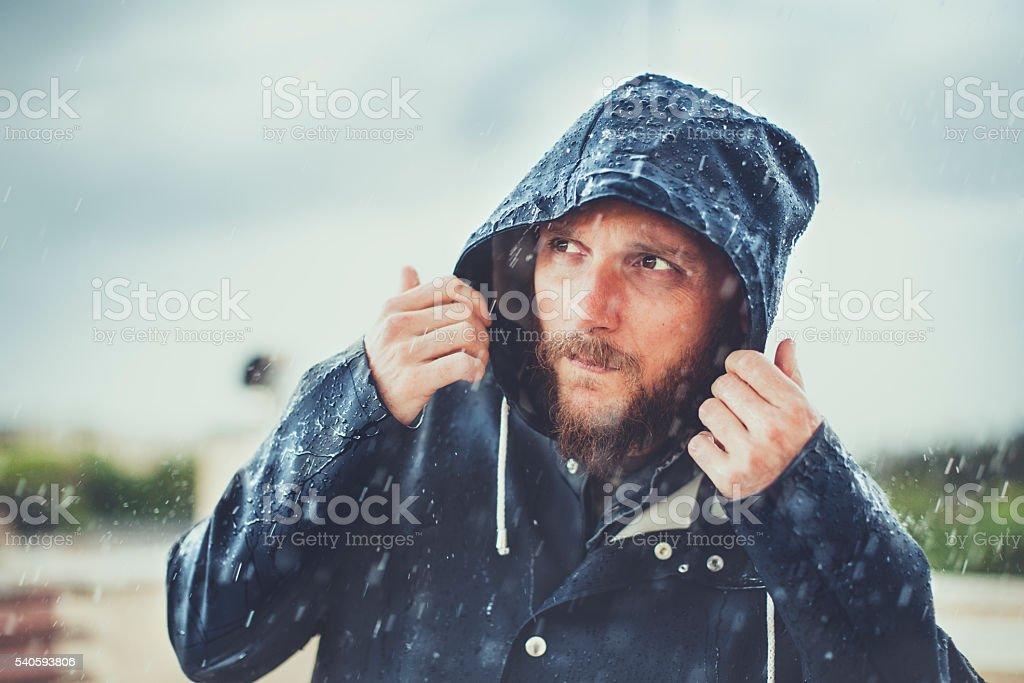 Man with raincoat under heavy rain stock photo