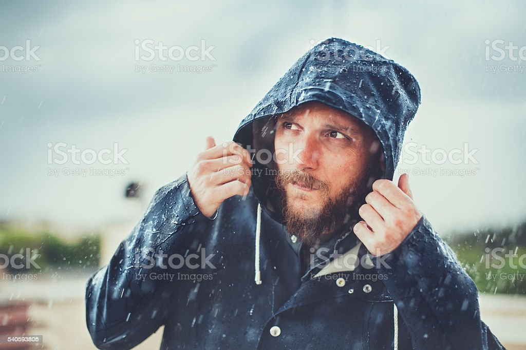 Man with raincoat under heavy rain stock photo