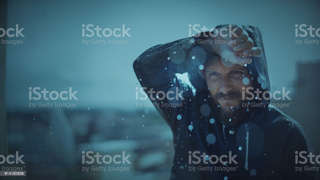Man with raincoat under storm and heavy rain stock photo