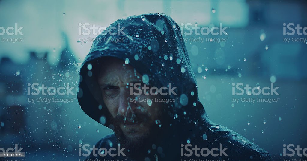 Man with raincoat under storm and heavy rain stock photo