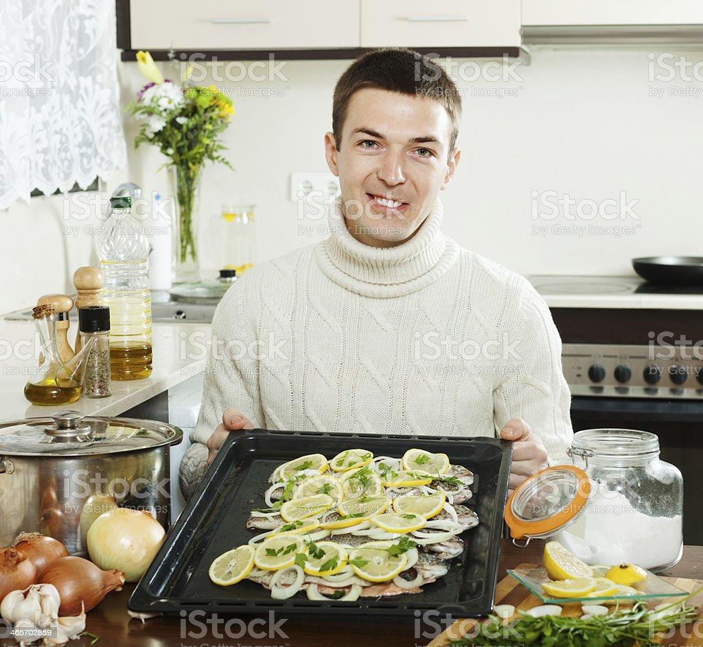 man with raw fish on roasting pan royalty-free stock photo