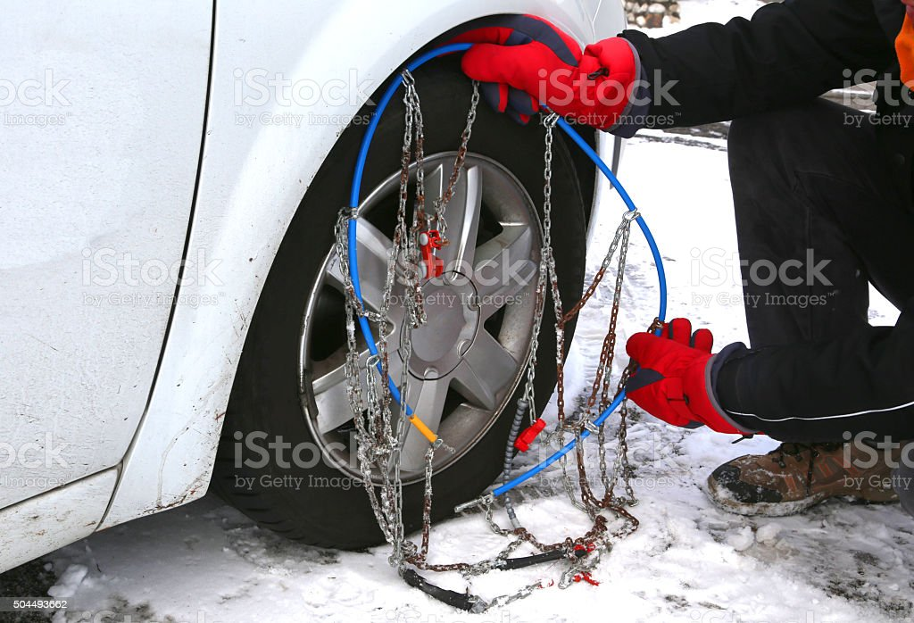 man with red gloves install snow chains stock photo