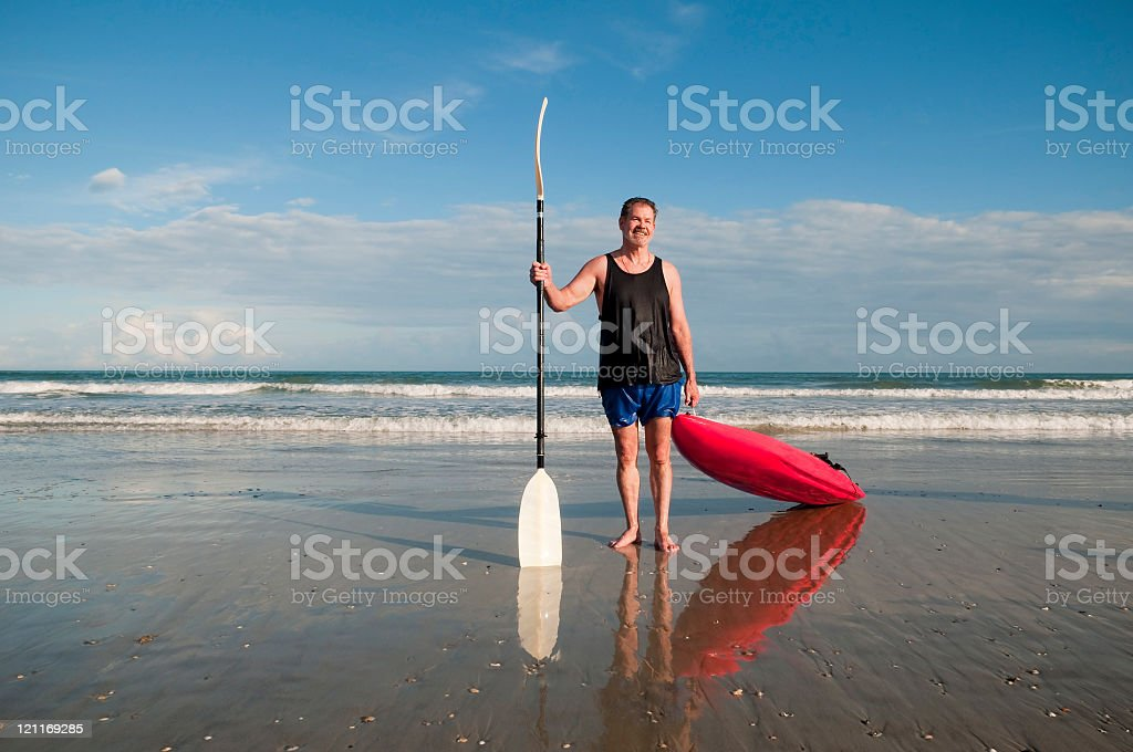 Man with red sea kayak at the beach royalty-free stock photo