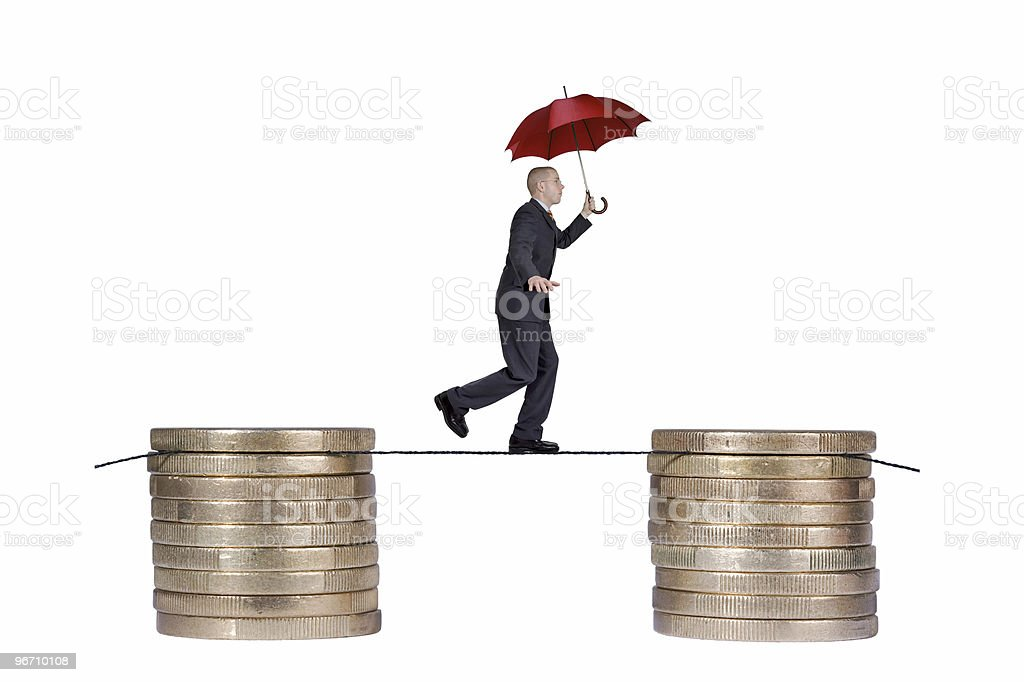 Man with red umbrella walking on rope between coin stacks royalty-free stock photo