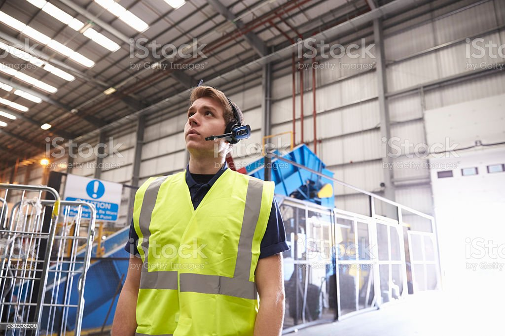 Man with reflective vest and headset standing in a warehouse stock photo