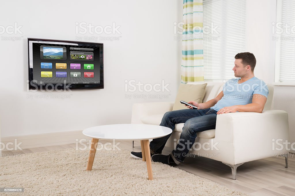 Man With Remote Control Watching Television At Home stock photo