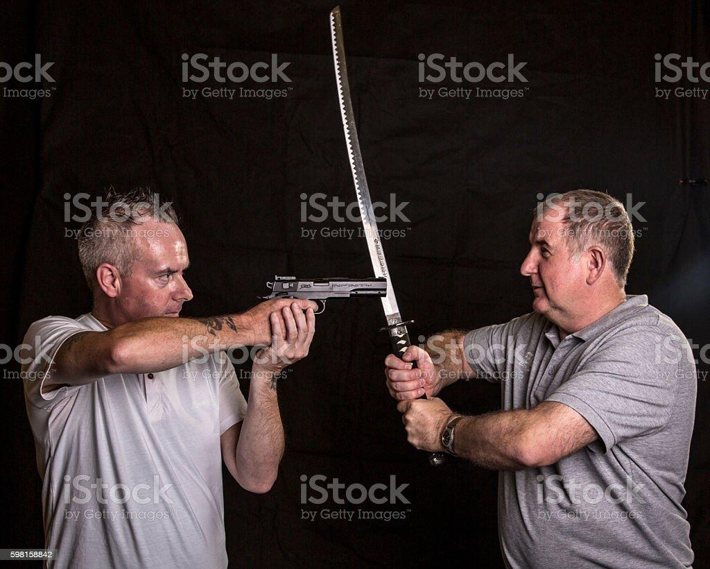 Man with revolver confronting swordsman stock photo