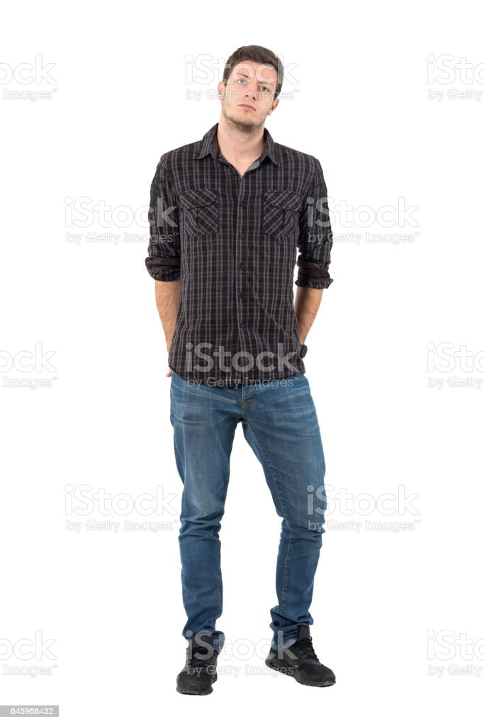 Man with rolled up sleeves with hands in back pockets stock photo