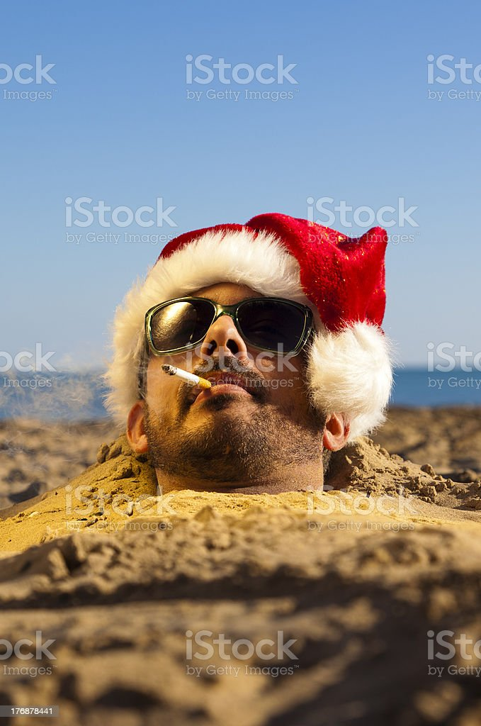 Man with Santa Claus Hat on the Beach. Humor. stock photo