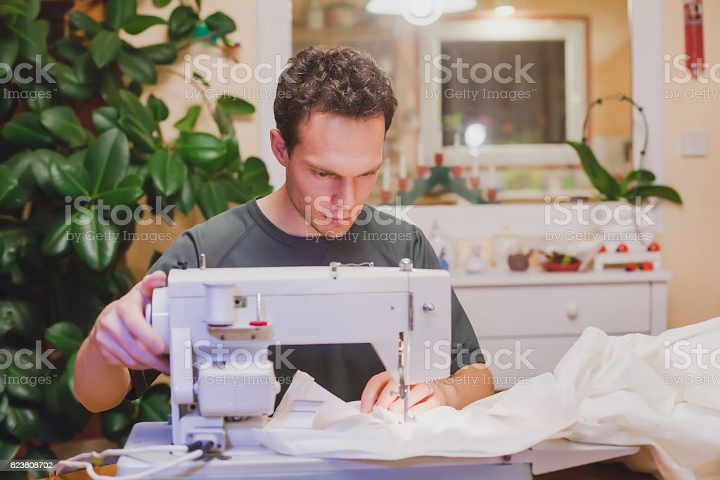 man with sewing machine at home stock photo