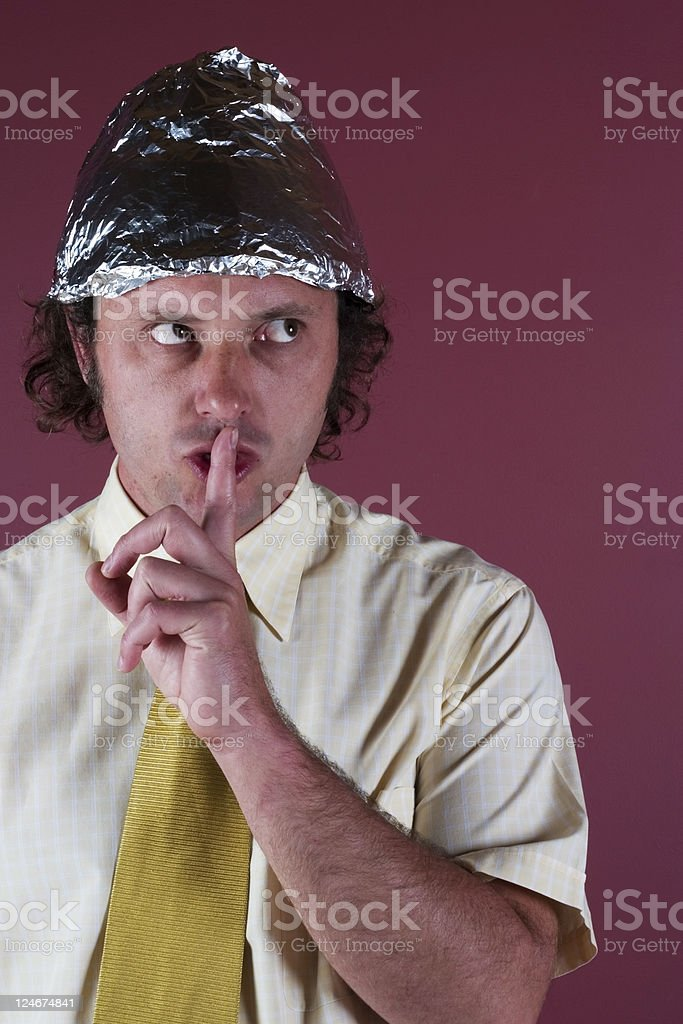 Man with shirt and foil hat on with his finger to his mouth stock photo